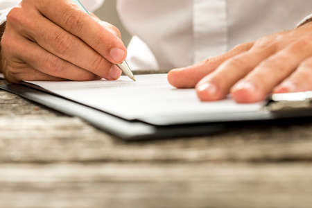 Photo pour Low angle view of male hand signing contract or subscription form with a pen on a rustic wooden desk. - image libre de droit
