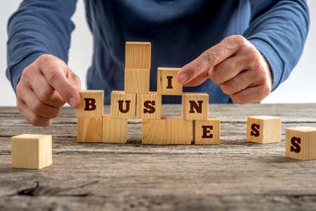 Foto de Close up of the hands of a man building the word Business with wooden blocks on a rustic table in a conceptual image. - Imagen libre de derechos