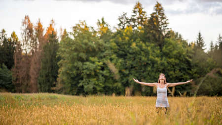 Young woman standing in the middle of autumn meadow with high golden grass looking up towards the sky with her arms spread widely as she enjoys fresh air and beauty of nature.