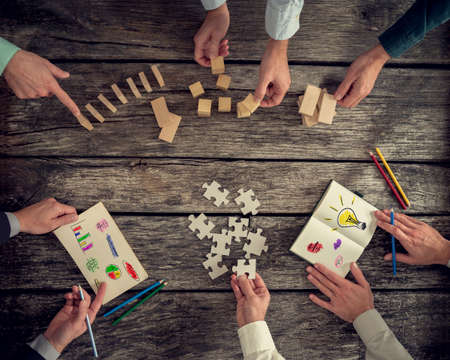 Foto de Businesspeople organizing business strategy while holding puzzle pieces, writing down ideas on paper and rearranging wooden blocks. Concept of brainstorming, management, innovation or creativity. - Imagen libre de derechos