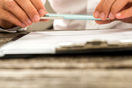 Closeup view of male hands holding pencil over paperwork on clipboard as man reads through terms and conditions. Conceptual of signing business contract, membership or legal document.