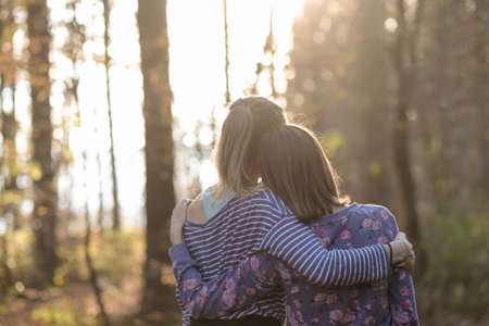 Foto de View from behind of two girlfriends or a lesbian couple standing in autumn woods leaning on each other with their arms around one another. - Imagen libre de derechos