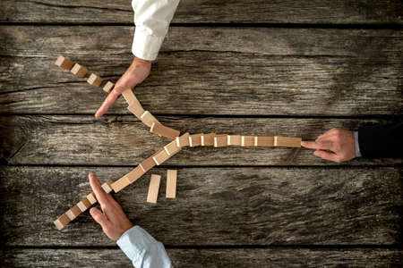 Foto de Top view of male hand pushing dominos placed in Y shape knocking them down and two other hands stopping them each on one side. Conceptual of crisis management in business. - Imagen libre de derechos