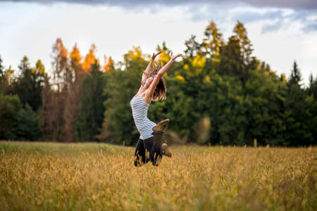 Happy cheerful young woman jumping in the air in the middle of golden meadow with high grass. Conceptual of enjoying life, happiness and life spirit.