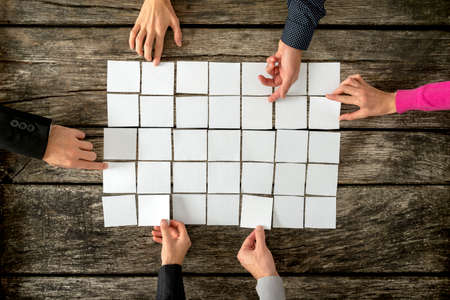 Foto de Top view of six hands, male and female, assembling a collage of blank white cards over textured wooden rustic boards. - Imagen libre de derechos