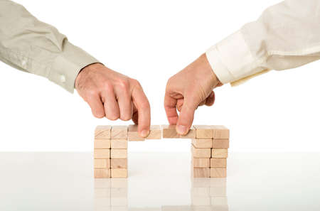 Photo pour Conceptual image of business merger and cooperation - two male hands joining effort to build a bridge of wooden pegs on a white desk with reflection over white background. - image libre de droit