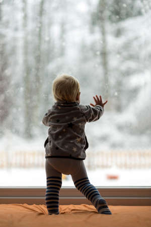 Toddler boy standing up against a window looking out to observe a snowy nature and forest.