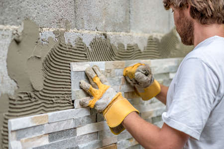 Photo pour Man pressing an ornamental tile into a glue on a wall with gloved hands in a DIY concept. - image libre de droit