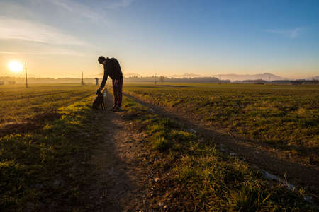 Photo pour Man standing on a country road leaning down to pet his black dog in a beautiful landscape with setting evening sun in background. - image libre de droit