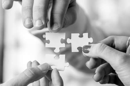 Black and white image of three people, male and female, holding puzzle pieces to match them. Conceptual of teamwork, cooperation and problem solving.