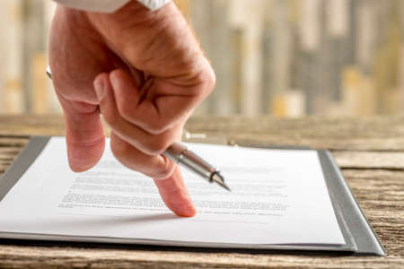 Closeup of male hand holding a pen pointing to a line at the end of a contract, document or application form ready for signature.