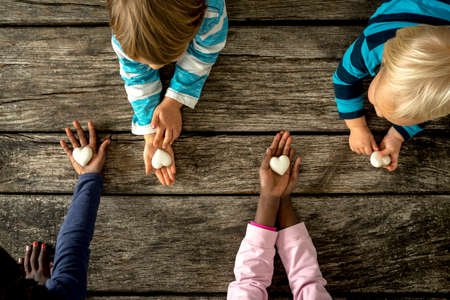 Photo pour Top view of four children of mixed races each holding a marble heart in hands. Conceptual of equality and friendship. - image libre de droit