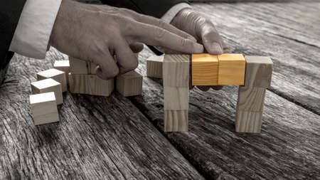 Closeup of businessman forming a bridge of small wooden blocks in greyscale image with two middle cubes connecting the two sides in standing out in vibrant colour.
