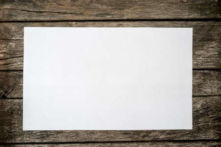 Photo pour Top view of blank white piece of paper on a textured rustic wooden desk. - image libre de droit
