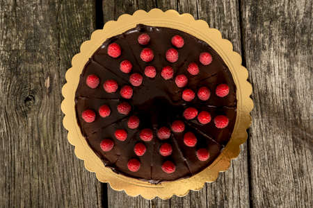 Photo pour Top view of delicious whole chocolate cake decorated with fresh ripe raspberries on a golden plate placed on textured rustic wooden desk. - image libre de droit