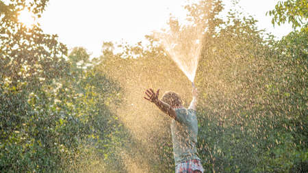 Man standing in summer nature surrounded by tall trees spraying himself with water hose as he holds his arms spread widely enjoying his vacation.