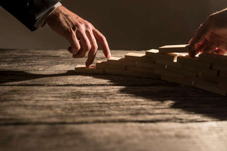 Foto de Closeup view of businessman arranging wooden pegs in to a staircase like structure for his colleague to walk his fingers up the steps. Conceptual of business cooperation, vision and success. - Imagen libre de derechos