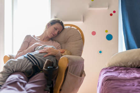 Photo for Tired young mother resting or napping on a rocking chair with baby sleeping in her lap inside a nursery room at day. - Royalty Free Image