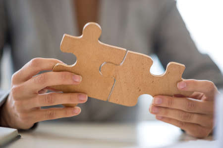 Photo pour Close up on unidentifiable business person with hands putting together two puzzle pieces. - image libre de droit