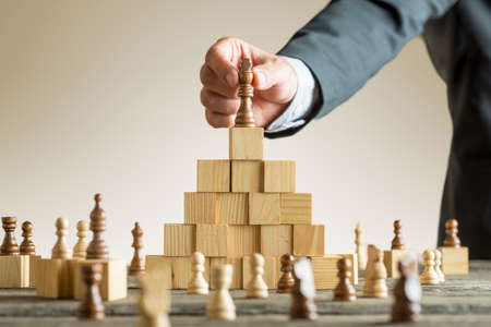 Photo pour Businessman placing a chess piece on a pyramid of wooden building blocks in a concept of success and achievement in a close up view of his arm. - image libre de droit