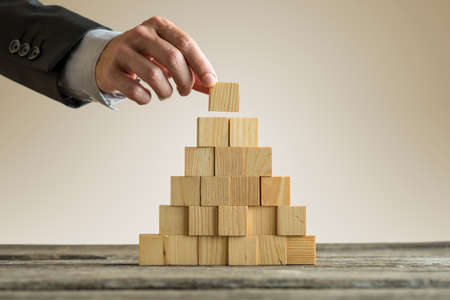 Foto de Closeup of businessman making a pyramid with empty wooden cubes. Concept of business hierarchy. - Imagen libre de derechos