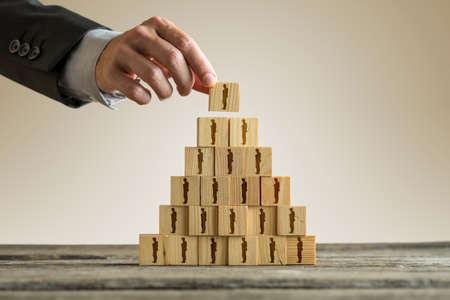 Foto de Businessman building a pyramid of wood blocks with people silhouettes, human resources and management concept. - Imagen libre de derechos