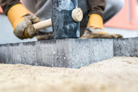 Photo pour Builder tamping down a new paving slab or brick with a large mallet in a close up view on the hands and tool. - image libre de droit