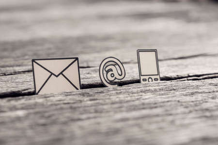 Photo pour Retro image of business communications concept with icons for email, a web address and telephone on rustic wooden table. - image libre de droit