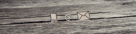 Photo pour Wide panorama view of at sign, mail and mobile phone icons stuck in between a crack in the wooden surface, toned retro effect. - image libre de droit