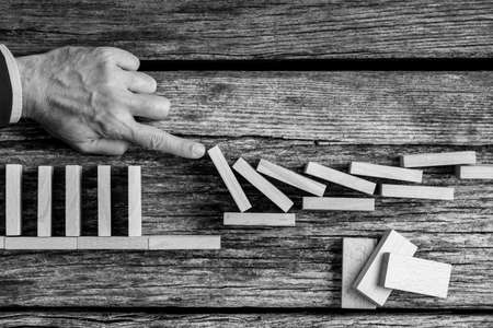 Conceptual monochrome image of the hand of a man avoiding collapse by stopping the destructive domino effect of wooden blocks.