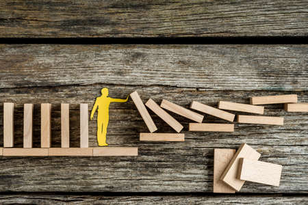 Photo pour Single man holding up falling wooden bricks in a conceptual image of a paper cutout silhouette on a rustic background. - image libre de droit