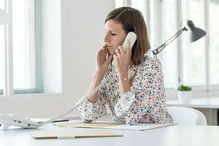 Photo pour Serious young business woman making a phone call as she sits at her desk in the office, side view. - image libre de droit