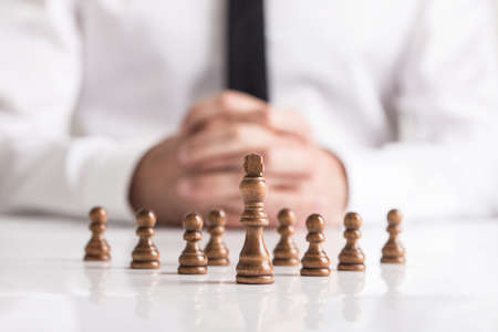 Photo pour Businessman with clasped hands planning strategy with dark chess figures on white table. - image libre de droit