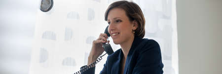 Photo pour Wide view image of a young businesswoman with smiling expression talking on a landline phone. - image libre de droit