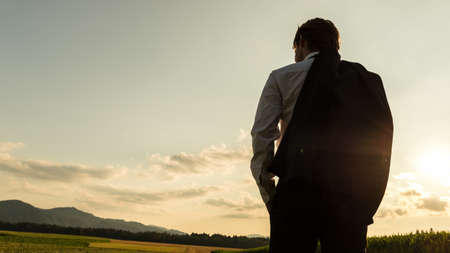 Photo pour View from behind of a businessman standing with jacket over his shoulder looking at beautiful nature of corn fields and meadows. - image libre de droit