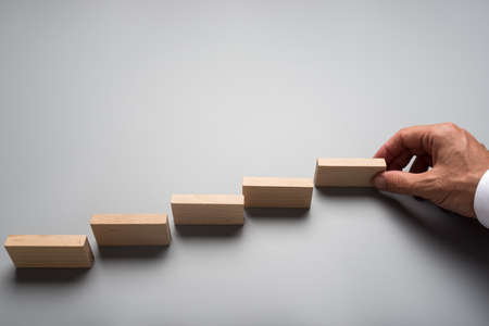 Businessman placing wooden pegs or dominos on grey surface. Conceptual of business vision and start up.