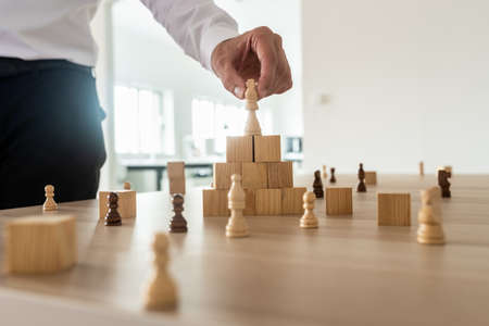 Photo for Business hierarchy concept with businessman placing chess figure of king on top of wooden stacked wooden blocks and other figures spread on office desk. - Royalty Free Image