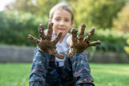Photo pour Happy toddler child showing his muddy hands toward the camera in a childhood innocence concept. - image libre de droit