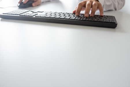 Photo pour Businessman using computer keyboard and a mouse, with copy space. - image libre de droit