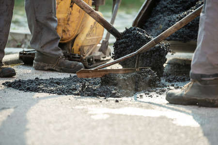 Foto de Two construction workers working together to patch a bump in the road with fresh asphalt. - Imagen libre de derechos
