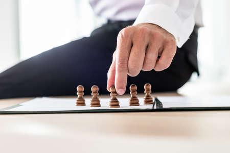 Business leader sitting on his desk making human resources decisions by positioning pawn chess pieces on paperwork.