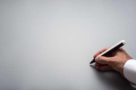 Photo pour Male hand writing on grey background with black marker. Plenty of copy space. - image libre de droit