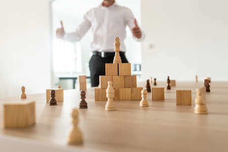 Photo for Chess figures and wooden locks positioned on office desk with king on top of a pyramid with businessman in background showing a thumbs up sign. - Royalty Free Image