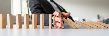 Photo pour Wide view image of business mediator stopping falling wooden dominos with his hand in a conceptual image of business crisis solution. - image libre de droit