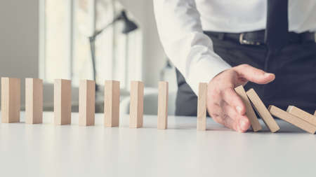 Photo pour Business crisis management concept - business mediator stopping falling dominos with his hand. - image libre de droit