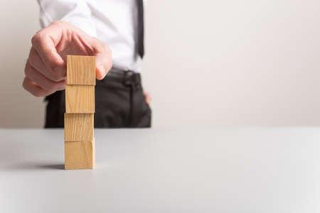 Foto de Businessman stacking four blank wooden cubes with plenty of copy space. - Imagen libre de derechos