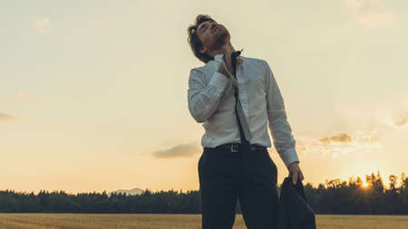 Photo pour Exhausted businessman standing in nature under an evening sky untying his tie relaxing the stress. - image libre de droit