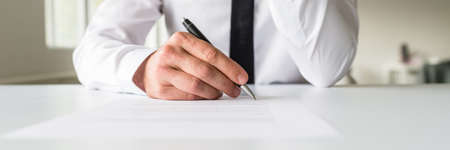 Photo pour Wide view image of businessman signing a contract or legal document on his white office desk. - image libre de droit