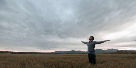 Photo for Young man standing in autumn meadow under cloudy evening sky with his arms wide open. - Royalty Free Image