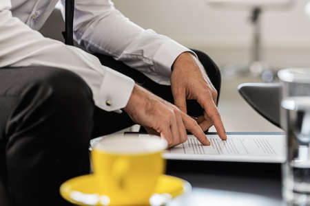 Photo pour Businessman sitting at an office coffee table proofreading a document or agreement with coffee cup next to him. - image libre de droit